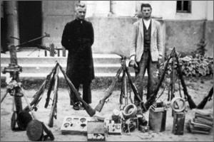 Reverend Wojciech Lorenc and Stanisław Niemiec, an undertaker, with an arms cache discovered by the UB in the attic of the church in Tryńcza on May 25, 1949.